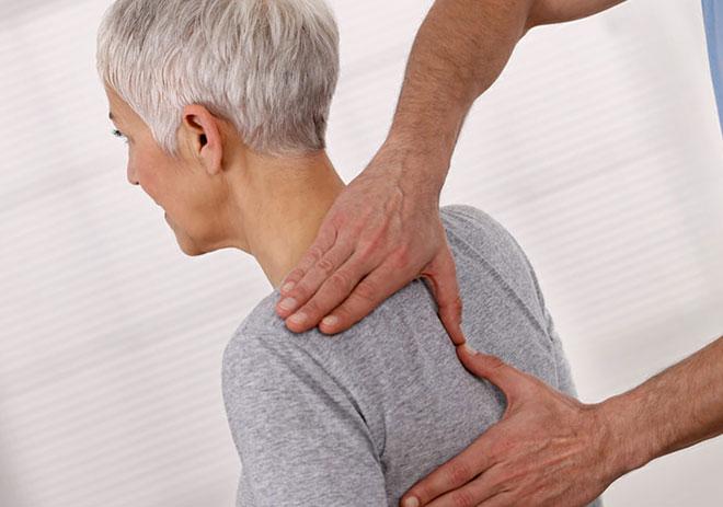 женщину с грудным остеохондрозом осматривает врач