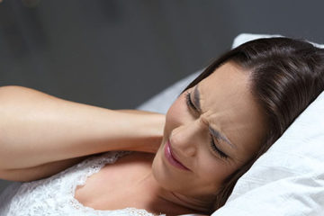 девушка мучается с болью в шее лежа в кровати